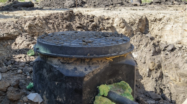 Installation, montage d'une nouvelle trappe d'égout en plastique dans le sol. construction de réseaux d'assainissement. installation d'un réservoir d'assainissement souterrain. réparation de routes, installation de trappes d'égout.