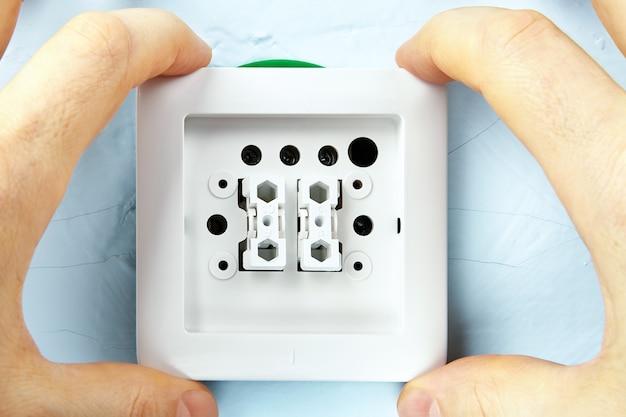 Installation d'un nouvel interrupteur d'éclairage par un électricien, travaux d'installation électrique.