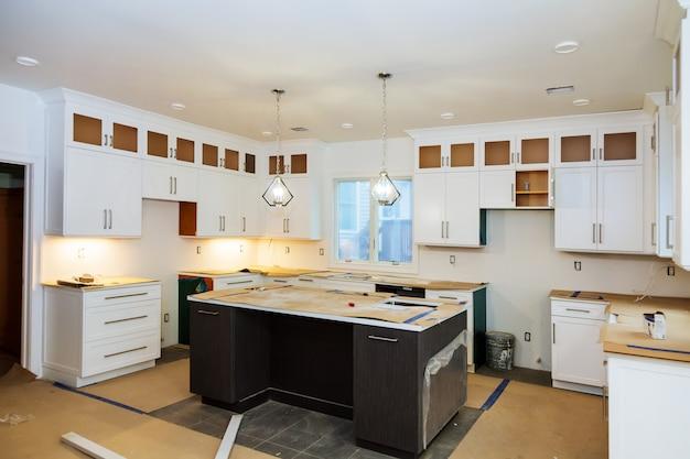 Installation d'une nouvelle plaque à induction dans une cuisine de cuisine moderne installation d'armoires de cuisine.
