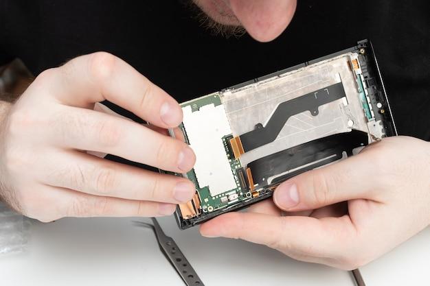 Installation de pièces détachées d'origine sur un téléphone portable. l'assistant récupère un smartphone à partir des détails