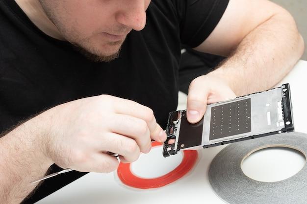 Installation de pièces détachées d'origine sur un téléphone portable. l'assistant supprime des fragments de l'écran du smartphone