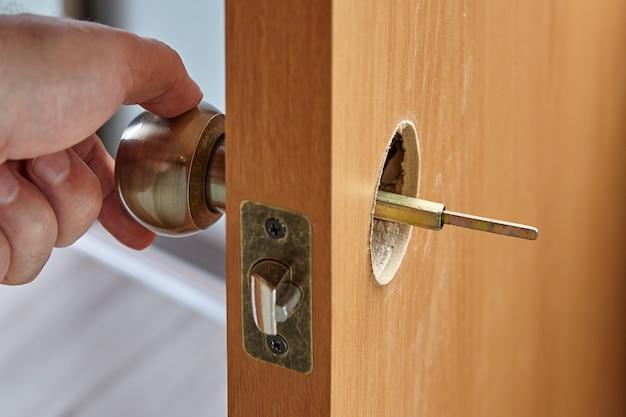 Installation d'une poignée de porte intérieure avec un axe visible du côté opposé.