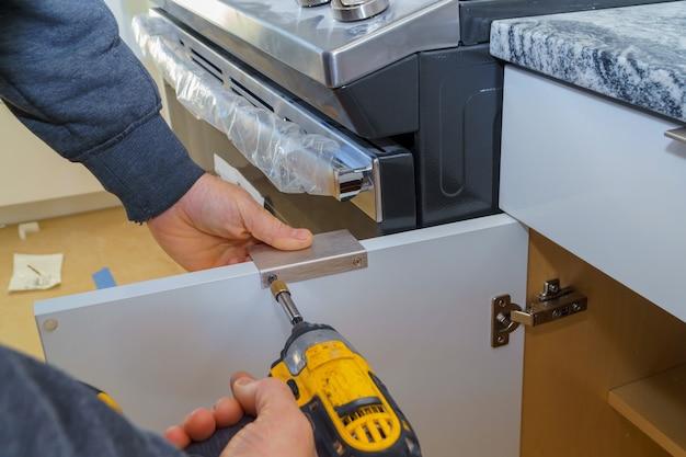 Installation de poignées de porte sur les armoires de cuisine avec un tournevis