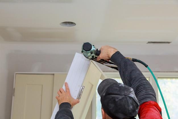 Installation des portes des pièces dans le travailleur du bois de la maison à l'aide d'un pistolet à clous