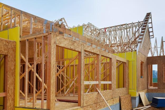 Installation de poutres en bois lors de la construction d'une maison à ossature photo d'une maison neuve en construction