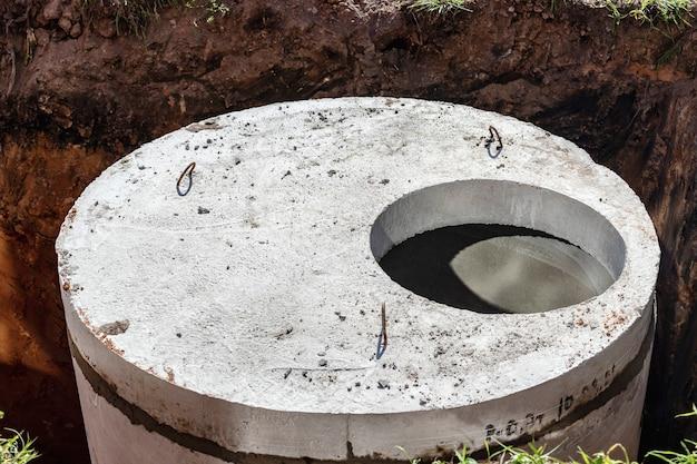 Installation de puits d'égout en béton dans le sol sur le chantier de construction. l'utilisation d'anneaux en béton armé pour les puisards, les fosses septiques à débordement. amélioration des puits et des égouts pluviaux.