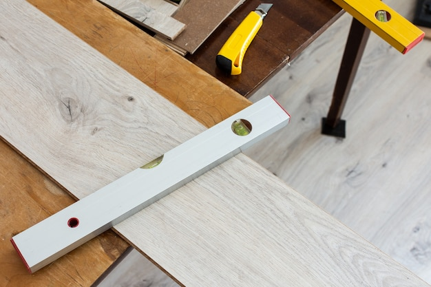 Installation de stratifié ou de parquet dans la pièce, ouvrier installant un sol stratifié en bois, marquant la longueur du stratifié