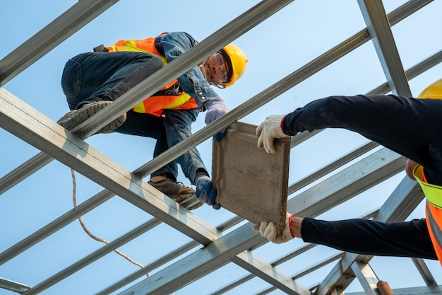 Installation de tuiles de toit en céramique par un ouvrier couvreur, concept de bâtiment résidentiel en construction.