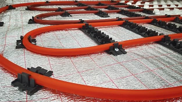 Installation de tuyaux de chauffage par le sol sur une membrane réfléchissant la chaleur.