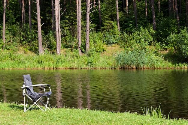 Installé en bord de rivière dans la forêt chaise pliante en métal pour la pêche, l'été
