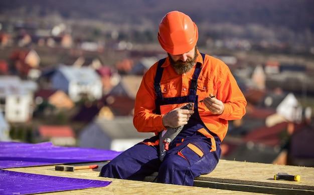Installez des pare-vapeur ou des couches d'isolant sur les toits plats. toit de construction de couvreur. toit de réparation maître. pose de toit plat. homme casque de travail fond de paysage extérieur. maison de construction.