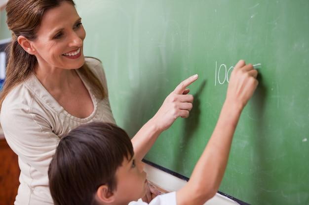 Un instituteur aide un écolier à faire un ajout