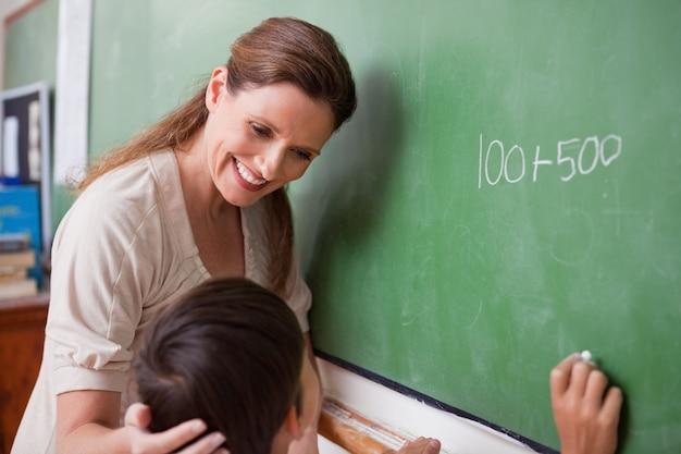 Un instituteur souriant aidant un écolier à faire un ajout