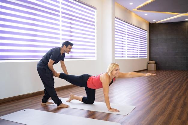 Instructeur aidant une femme à faire un oiseau pose au cours de yoga