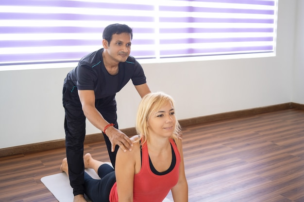 Instructeur aidant la femme à faire la pose de chien face à la hausse