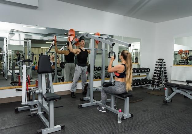 Instructeur aidant la femme à soulever l'équipement de sport dans la salle de sport
