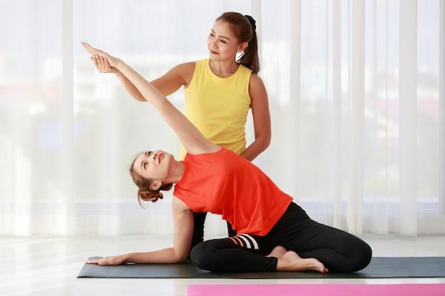 Instructeur asiatique aidant une étudiante nouvelle venue à étirer son corps pendant une leçon de yoga contre une fenêtre avec un rideau en studio
