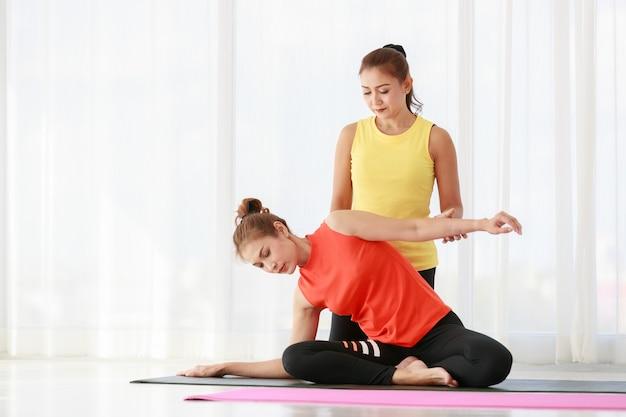 Instructeur asiatique aidant une étudiante nouvelle venue à étirer son corps pendant une leçon de yoga contre la fenêtre