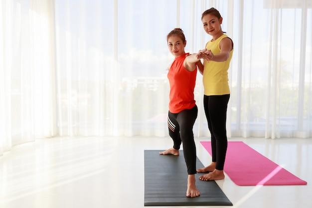 Instructeur asiatique complet du corps soutenant une étudiante nouvelle venue faisant une pose de guerrier pendant une séance de yoga dans un studio lumineux