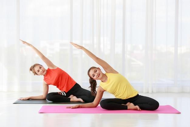 Instructeur asiatique dirigeant et enseignant un échantillon pour une étudiante nouvelle venue pour étirer le corps pendant le cours de yoga contre une fenêtre avec un rideau en studio
