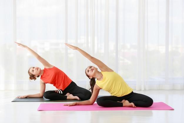 Instructeur asiatique dirigeant et enseignant un échantillon pour une étudiante nouvelle venue pour étirer le yoga corporel