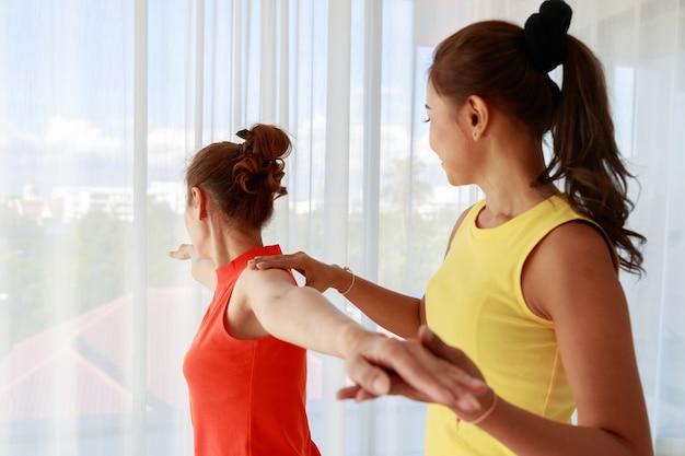 Instructeur asiatique soutenant une étudiante nouvelle venue faisant une pose de guerrier pendant une séance de yoga dans un studio lumineux