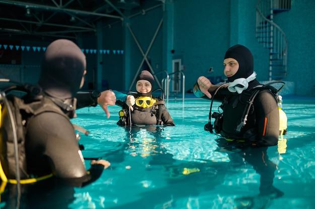 Instructeur et deux plongeurs, leçon en école de plongée