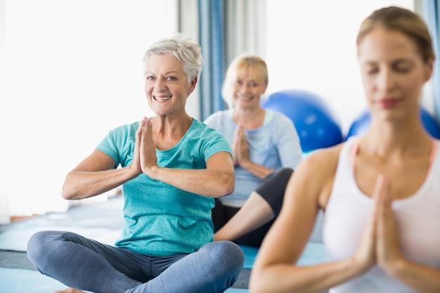 Instructeur effectuant du yoga avec des personnes âgées