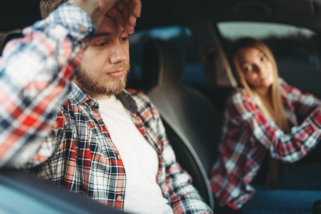 Instructeur et étudiante souriant dans le véhicule