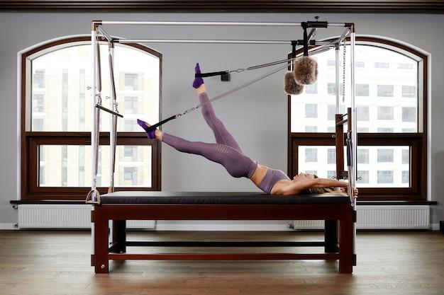 L'instructeur fait des exercices sur le réformateur, une belle fille s'entraîne sur le simulateur de réformateur moderne pour travailler les muscles profonds, l'équipement de réformateur modernisé pour le pilates et le yoga.