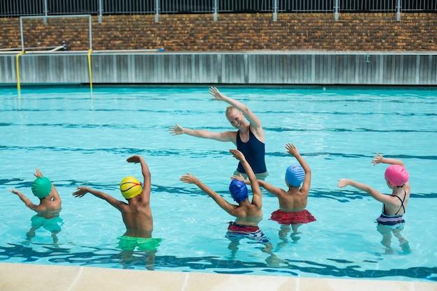 Instructeur féminin enseignant aux enfants dans la piscine