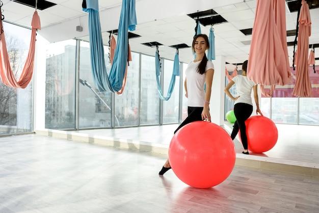 Instructeur de fitness jeune et mince posant avec grosse balle
