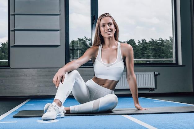 Instructeur de fitness posant dans la salle de gym