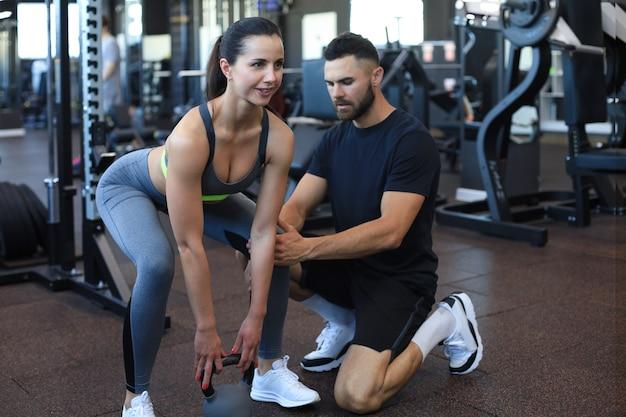 Instructeur de fitness s'exerçant avec son client au gymnase.