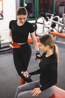 Instructeur de gym guidant la femme pendant l'exercice avec haltère