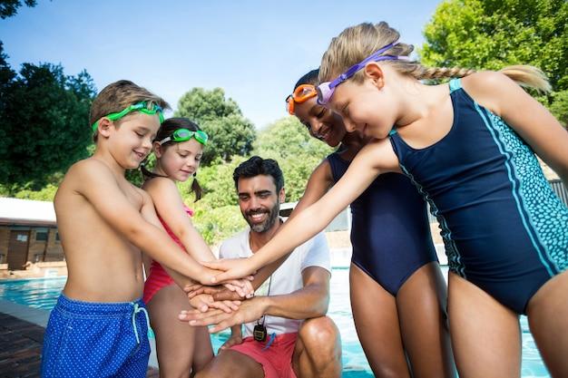 Instructeur masculin et enfants empiler les mains au bord de la piscine