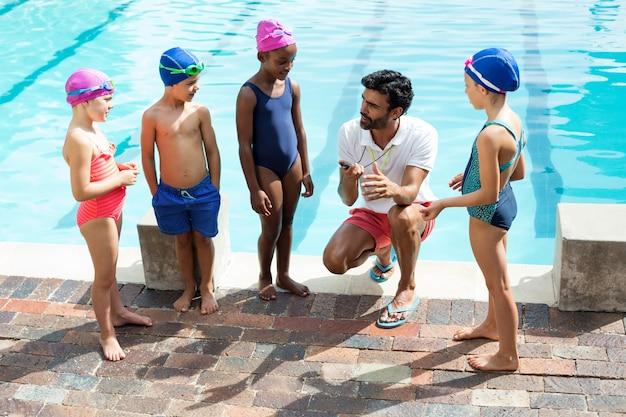 Instructeur masculin de la formation des enfants au bord de la piscine