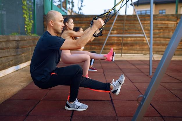 Instructeur masculin et groupe de femmes faisant de l'exercice sur un terrain de sport en plein air, entraînement de remise en forme