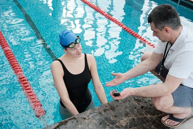 Instructeur masculin mature montrant le temps au tour sur chronomètre pour nageur tout en discutant de la formation avec elle