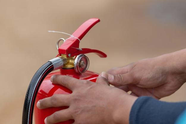 Instructeur montrant comment utiliser un extincteur d'incendie sur un feu d'entraînement