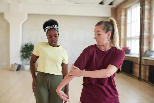 Instructeur montrant le mouvement au danseur pendant l'entraînement sportif en studio de danse