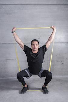 Instructeur personnel effectuant des exercices avec groupe de fitness