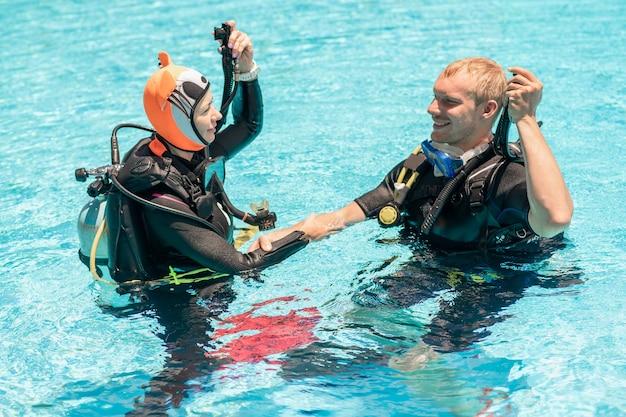 L'instructeur de plongée sous-marine démontre une compétence à un étudiant dans une piscine