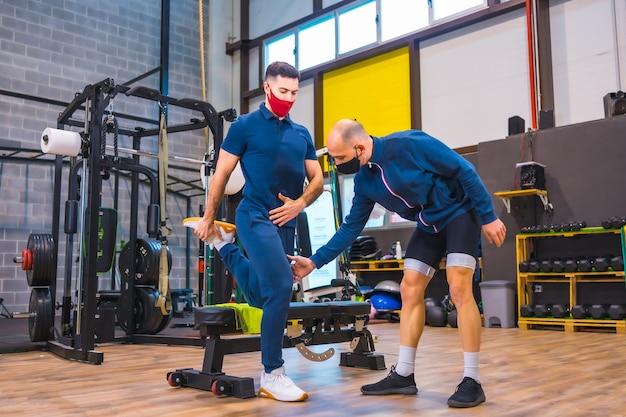 Instructeur en salle de sport corrigeant les exercices de l'athlète dans la pandémie de coronavirus