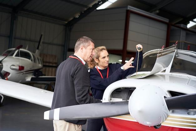 Instructeur de vol féminin enseignant à son élève comment faire l'entretien de l'avion