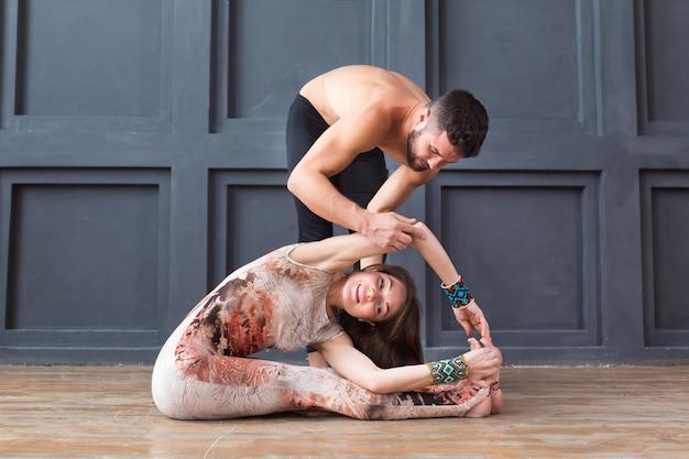 Un instructeur de yoga aide une jeune femme à faire de l'exercice