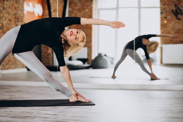 Instructeur de yoga féminin exerçant au gymnase