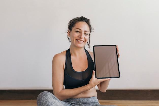 Instructeur de yoga montrant un fond d'écran de téléphone mobile tablette numérique