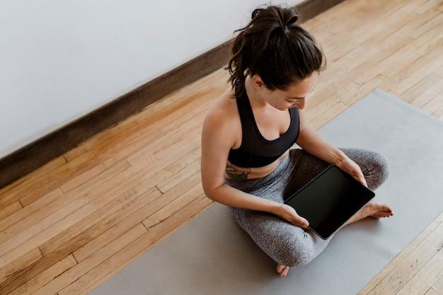 Instructeur de yoga utilisant un fond d'écran de téléphone portable pour tablette numérique