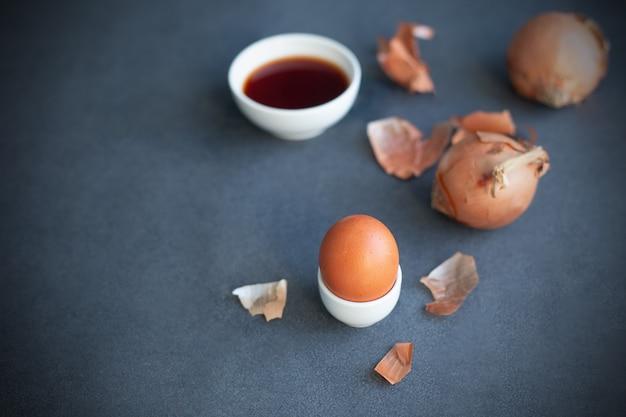 Instructions comment colorer les œufs de pâques avec un colorant naturel. couleur orange de la peau d'oignon. copiez l'espace. fond gris